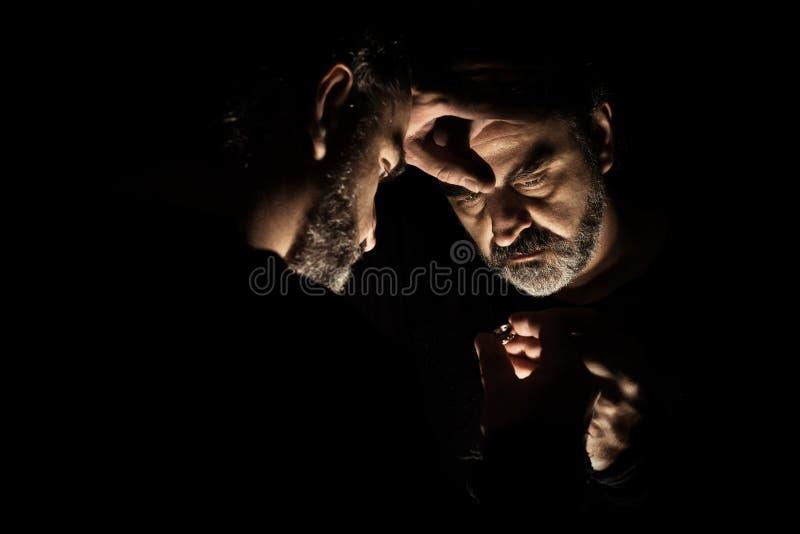 Homme de désespoir la position, triste et isolée devant un miroir photographie stock