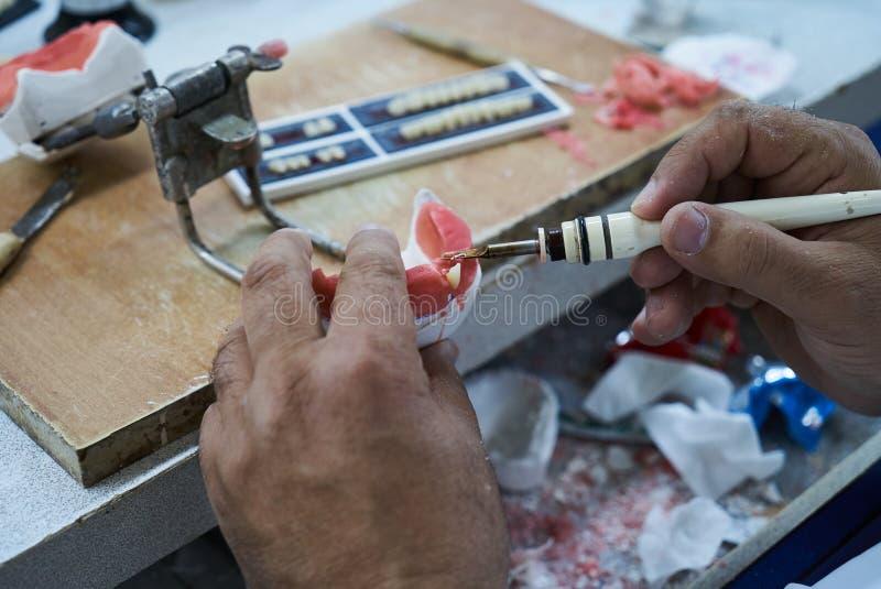 Homme de dentiste de technicien dentaire travaillant avec des dentiers photographie stock libre de droits