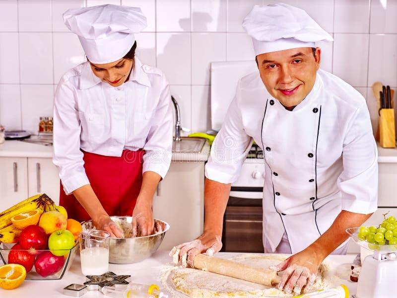 Homme de femme dans le chapeau de chef faisant cuire le gâteau de fruit photos libres de droits