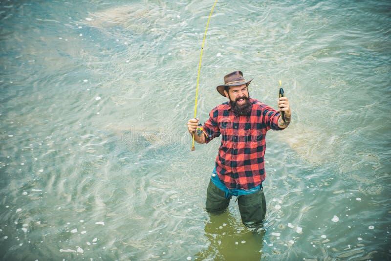 Homme de Fisher pêchant avec la bobine de rotation La pêche de mouche est la plus renommée comme méthode pour attraper la truite  photographie stock libre de droits