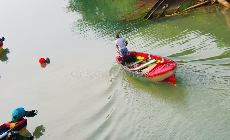 Homme de Fisher voyageant en bateau photographie stock libre de droits
