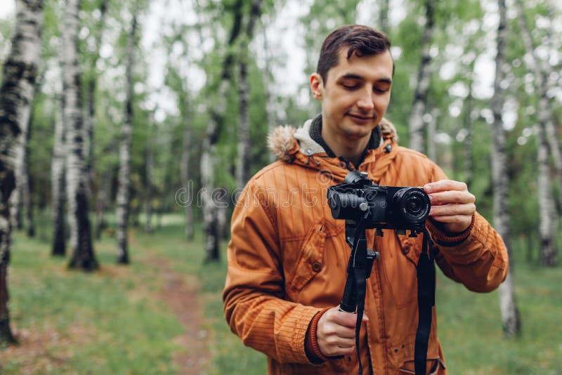 Homme de forêt de ressort de pelliculage de Videographer utilisant le steadicam et la caméra pour faire la longueur Pousse visuel photo stock