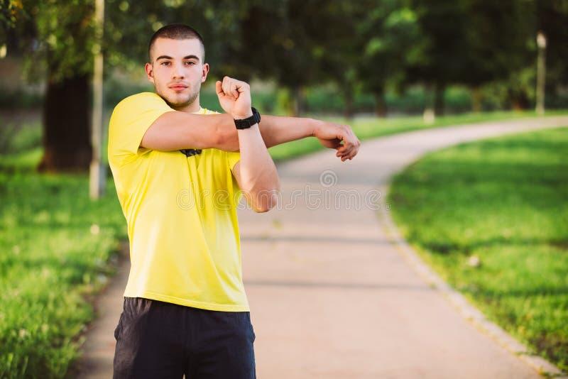 Homme de forme physique étirant l'épaule de bras avant séance d'entraînement extérieure Athlète masculin sportif en parc urbain r photos libres de droits
