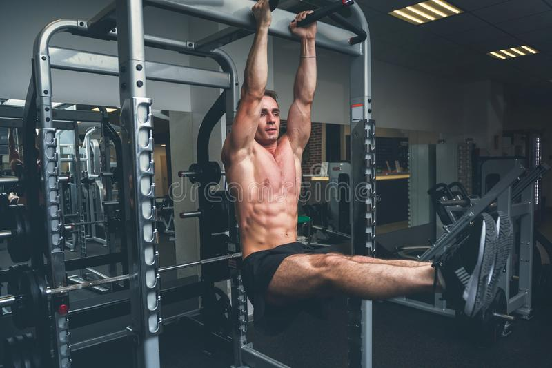 Homme de forme physique accrochant sur la barre horizontale exécutant des augmenter de jambes, dans le gymnase photographie stock