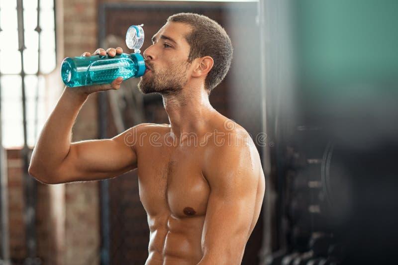 Homme de forme physique buvant de la bouteille d'eau photo libre de droits