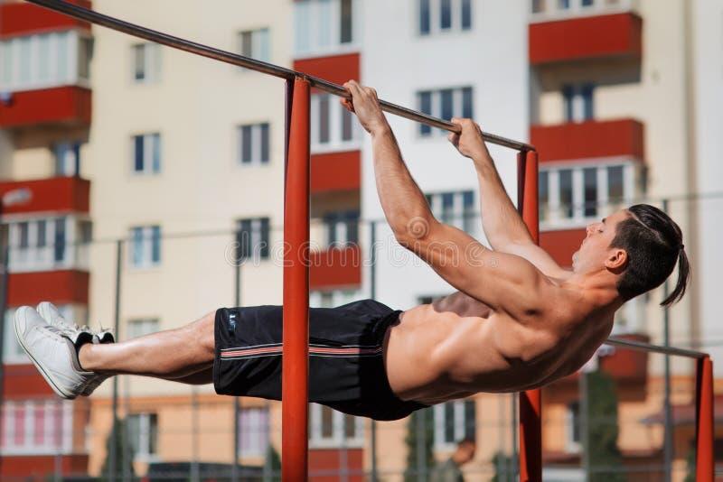 Homme de forme physique faisant des séances d'entraînement d'estomac sur la barre horizontale dehors images libres de droits