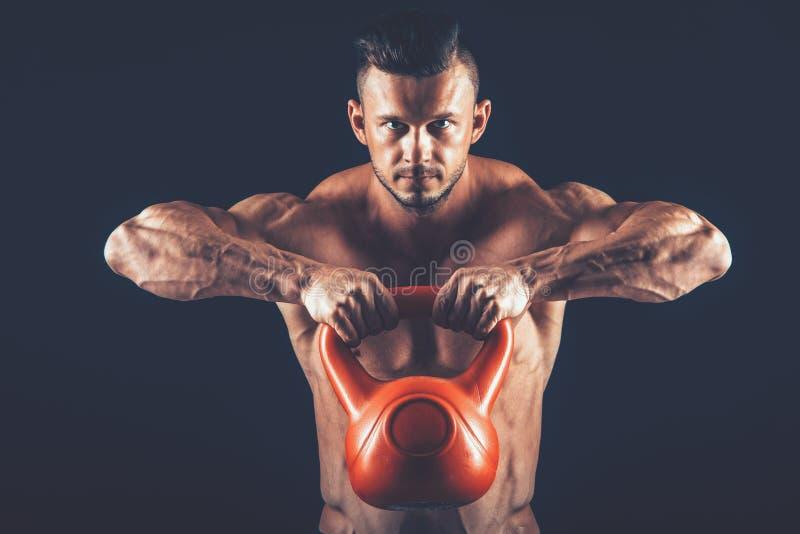 Homme de forme physique faisant une formation de poids en soulevant le kettlebell lourd image libre de droits