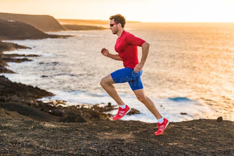 Homme de forme physique de sport de coureur de traînée courant ultra sur la falaise d'océan dans le coucher du soleil Formation p photos stock