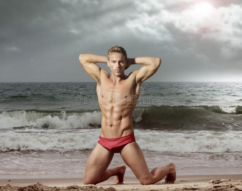 Homme de forme physique sur la plage photo stock