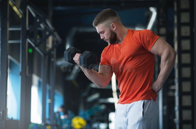 Homme de forme physique tenant une haltère dans le gymnase images stock