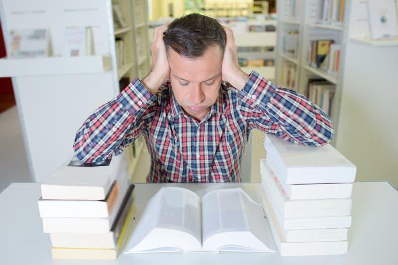Homme de Frusrated se penchant sur deux livres de piles image stock