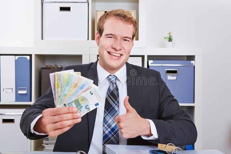 Homme de gain d'affaires tenant des pouces photographie stock
