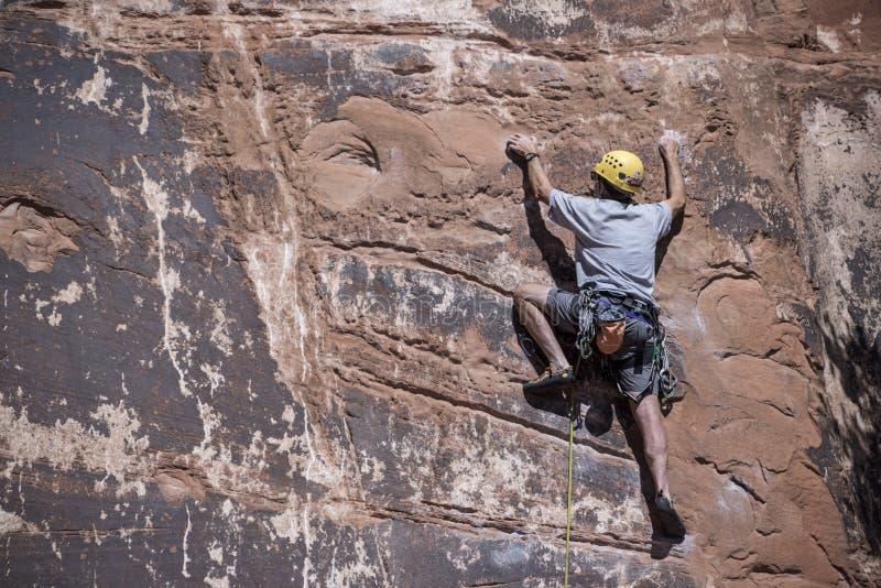 Homme de grimpeur de roche montant librement des prises et des équilibres sur des falaises de grès rouge pour placer des pitons e images libres de droits