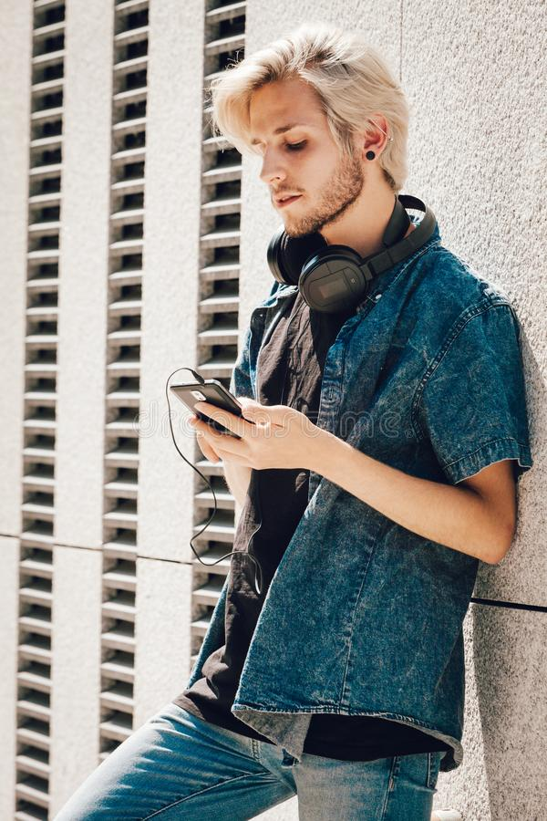 Homme de hippie avec des écouteurs regardant le téléphone photo libre de droits