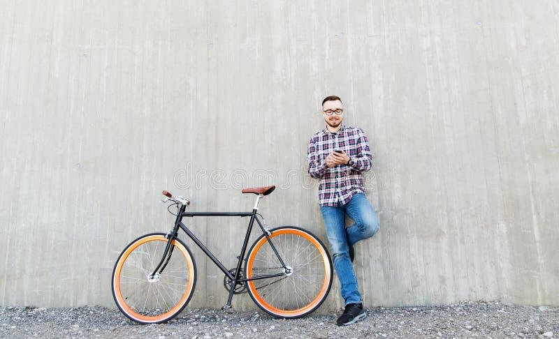 Homme de hippie dans des écouteurs avec le smartphone et le vélo image libre de droits