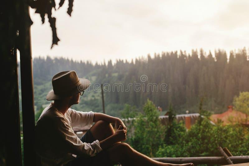 Homme de hippie s'asseyant sur le porche de la maison en bois regardant des bois i photographie stock