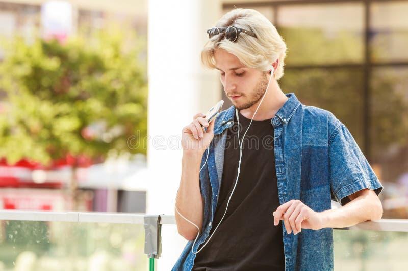 Homme de hippie se tenant sur la musique de écoute de rue de ville image libre de droits