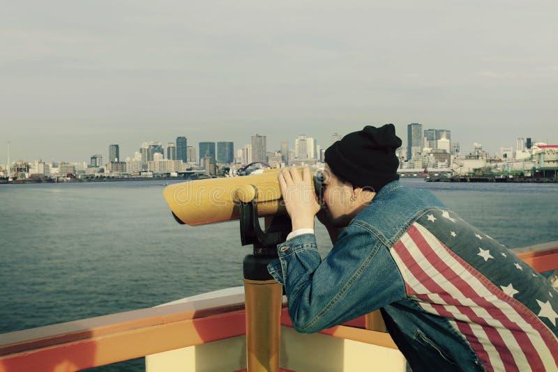 Homme de hippie utilisant la veste de jeans de drapeau américain regardant par la lentille binoculaire contre le bâtiment urbain photographie stock libre de droits
