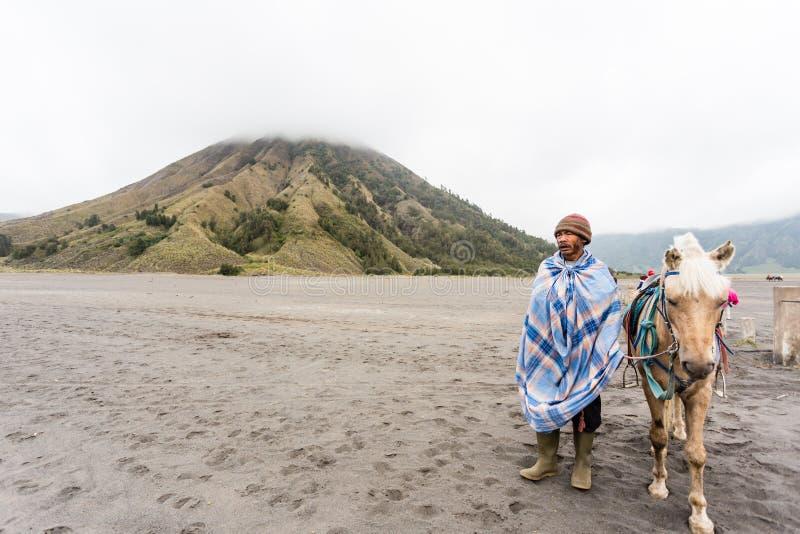 Homme de l'Indonésie avec le cheval pour le loyer de touristes au bâti Bromo image stock