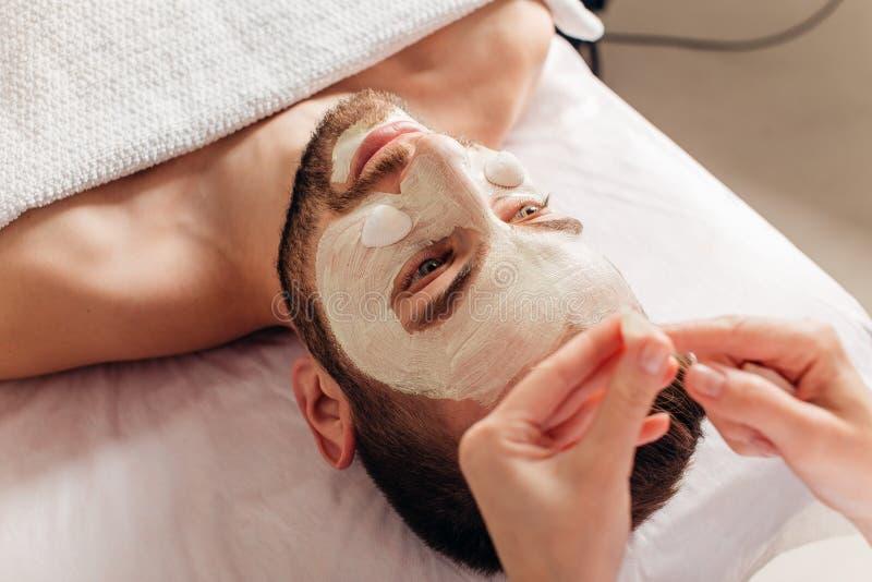 Homme de la procédure cosmétique de masque dans le salon de station thermale images libres de droits