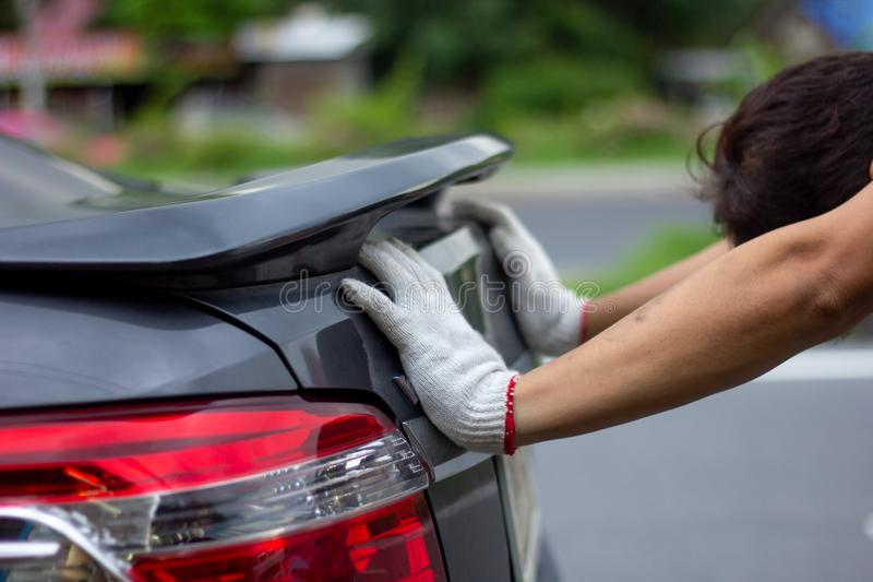 Homme de mécanicien poussant une voiture cassée en bas de la vue de côté de route photographie stock libre de droits