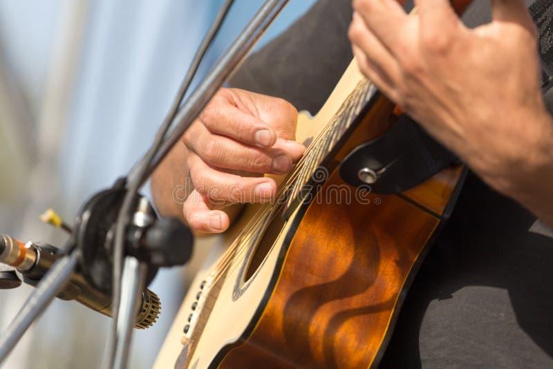 Homme de main jouant la guitare photos stock