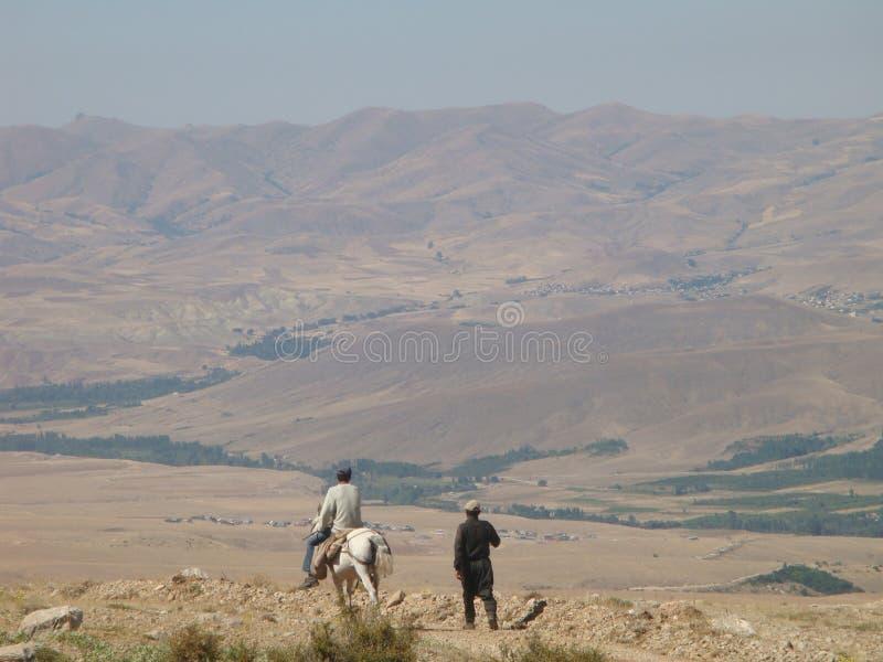 Homme de marche vu par derrière avec à son côté autre sur un cheval blanc dans les montagnes de la Turquie images stock