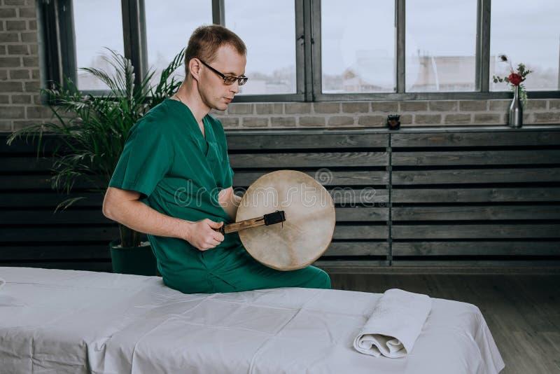 Homme de masseur tenant un tambour de basque dans la douille photo libre de droits