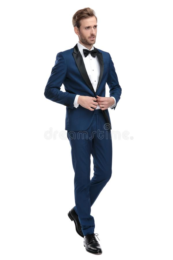 Homme de mode dans le costume bleu boutonnant sa veste de salon photo stock
