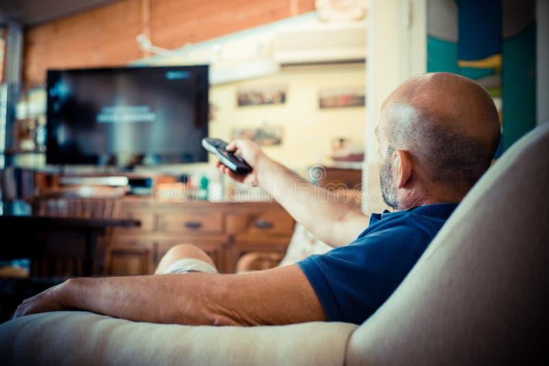 Homme de Moyen Âge regardant la TV image libre de droits