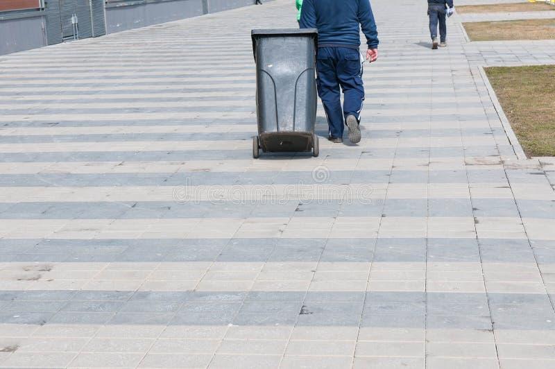 Homme de nettoyage avec la poubelle en plastique image stock