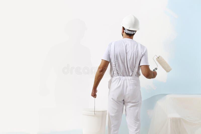 Homme de peintre au travail avec un rouleau et un seau de for Nettoyer un rouleau de peinture