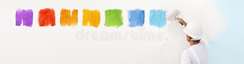 Homme de peintre avec des échantillons de couleur de dessin de peinture de rouleau sur le blanc photos libres de droits