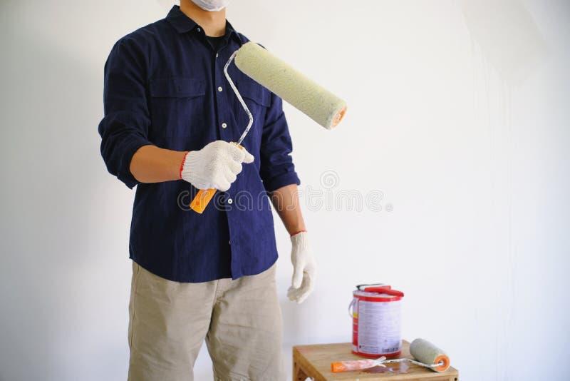 Homme de peintre du travail de peinture de pièce avec le rouleau photos stock