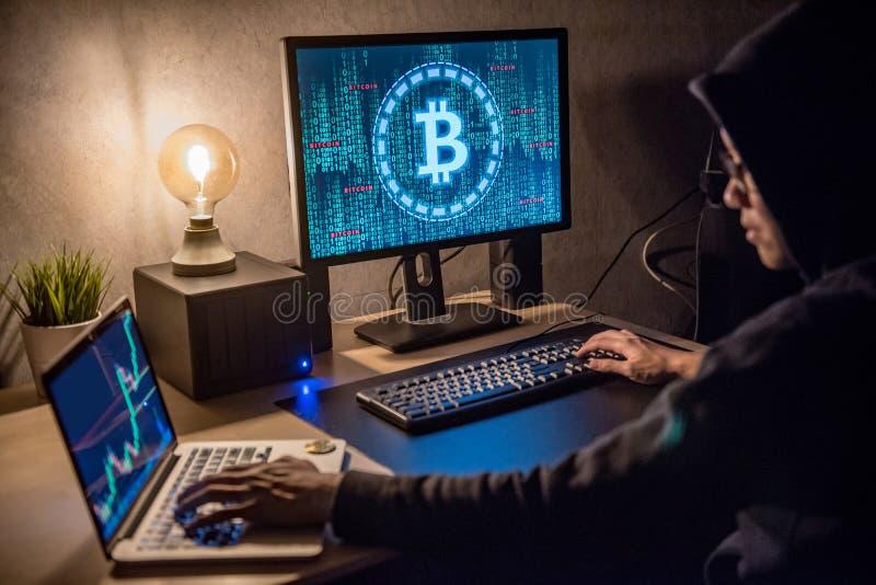 Homme de pirate informatique à l'aide de l'ordinateur pour le blanchissage numérique de devise image stock