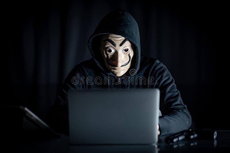 Homme de pirate informatique dans le masque de mystère utilisant l'ordinateur portable image stock
