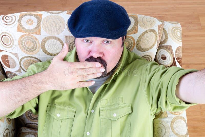 Homme de poids excessif dans le baiser de soufflement de béret photographie stock
