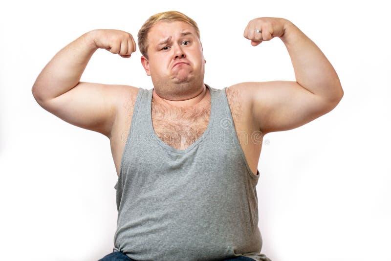 Homme de poids excessif drôle de sports fléchissant son muscle d'isolement sur le fond blanc images stock