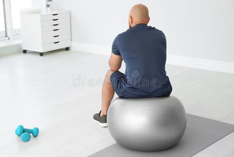 Homme de poids excessif fatigué s'asseyant sur la boule de forme physique photo stock