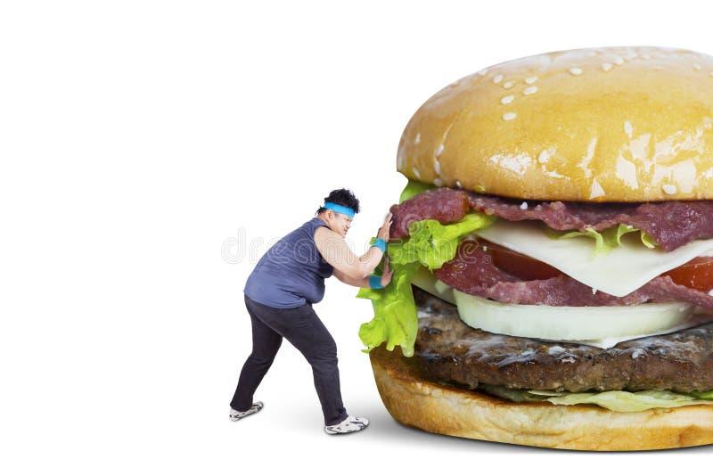 Homme de poids excessif poussant le grand hamburger photo libre de droits