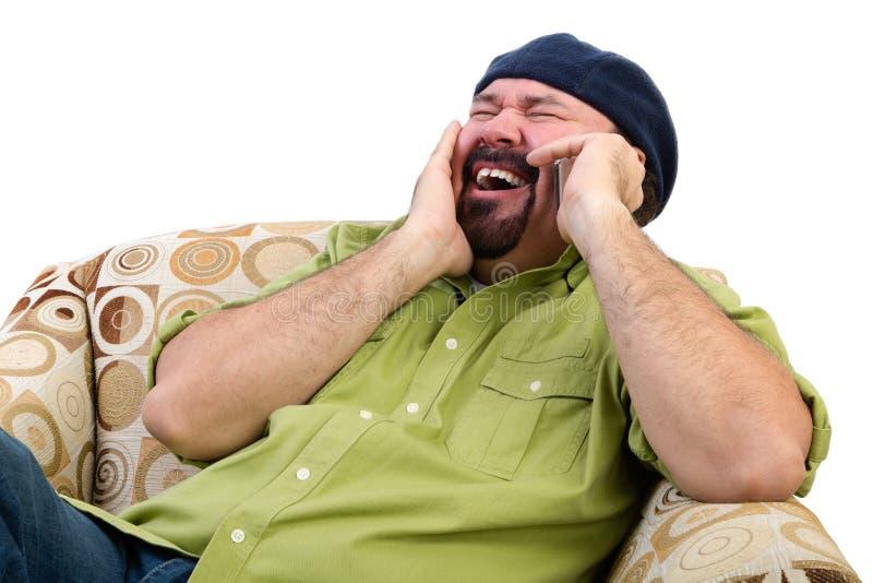 Homme de poids excessif riant dans la chaise avec le mobile photo stock