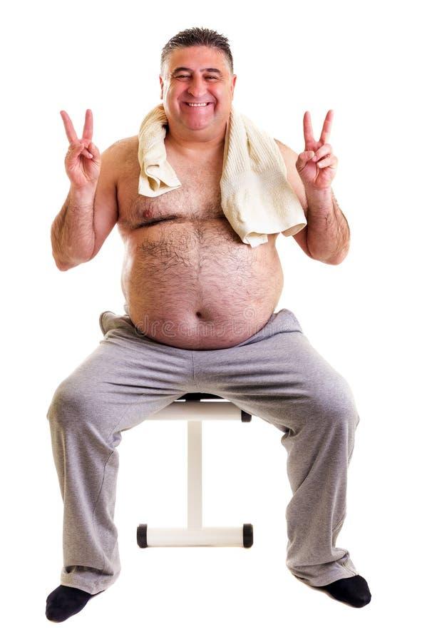 Homme de poids excessif se reposant sur un banc pour des abdominals et montrant Vic photographie stock