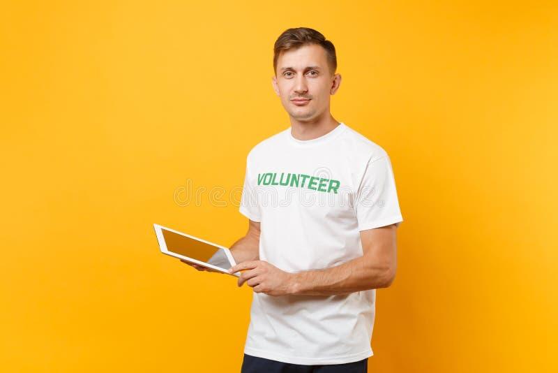Homme de portrait dans le T-shirt blanc avec le volontaire écrit de titre de vert d'inscription utilisant l'ordinateur de dactylo image libre de droits