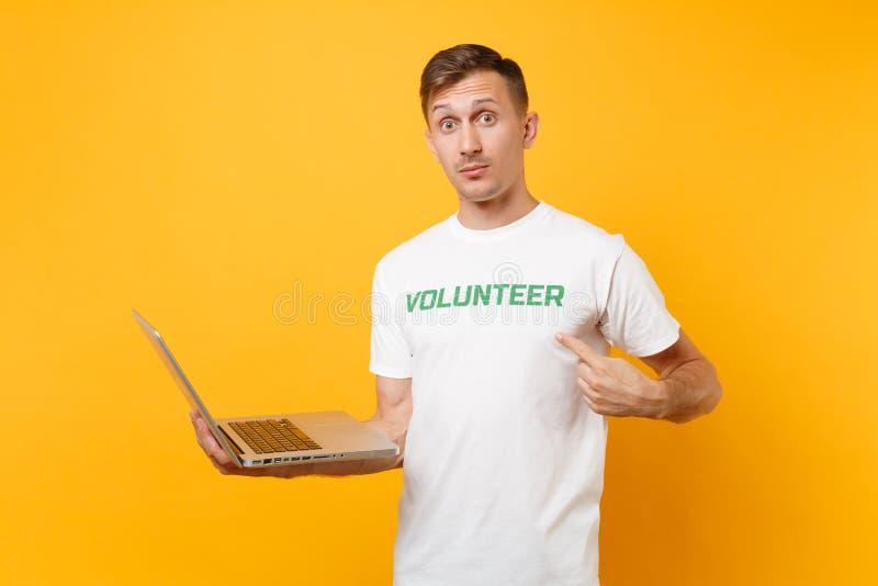 Homme de portrait dans le T-shirt blanc avec le volontaire écrit de titre de vert d'inscription utilisant l'ordinateur de dactylo photo libre de droits