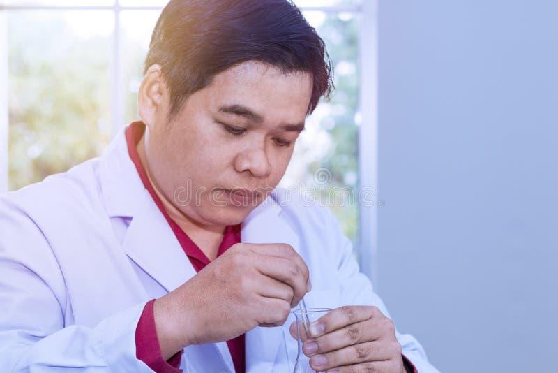 Homme de portrait de scientifique mûr dans un manteau blanc tenant le tube à essai images stock