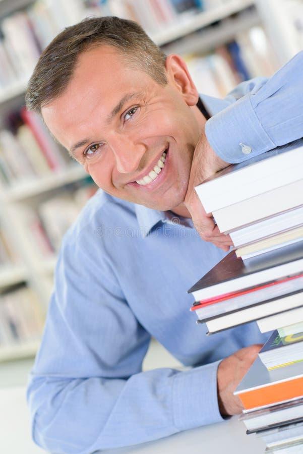 Homme de portrait se penchant sur des livres de pile photo libre de droits