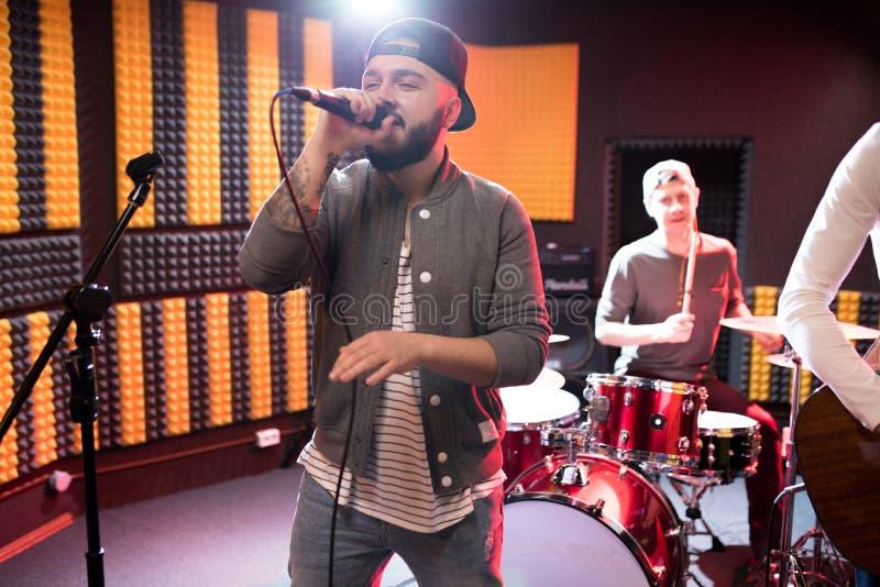 Homme de premier plan de bande chantant à la répétition image stock