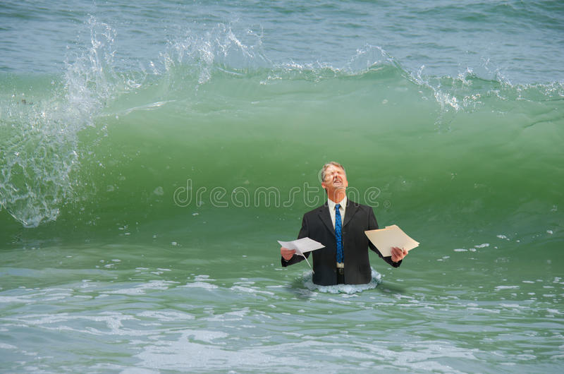 Homme de pression d'affaires obtenant frappé par la vague photo stock