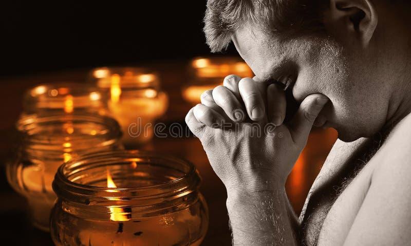 Homme de prière avec des bougies image libre de droits