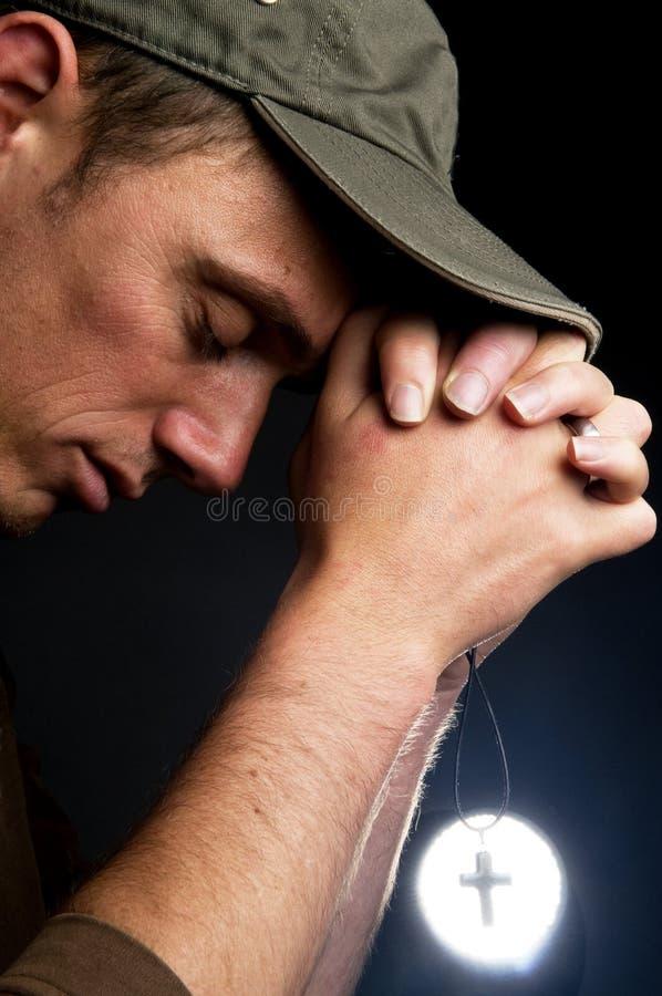 Homme de prière retenant une croix image libre de droits